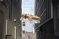 Mature man with longboard in an alley - WESTF23561