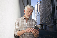 Mature man in the city using smartphone - WESTF23567