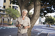 Mature man leaning against tree, holding sunglasses - WESTF23570