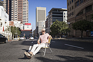 Mature man sitting on chair in the street, wearing sunglasses - WESTF23573