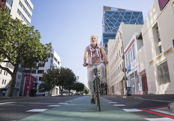 Mature man riding bicycle in the city - WESTF23576