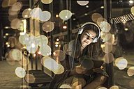 Portrait of young woman with headphones and tablet waiting at station by night - UUF11627