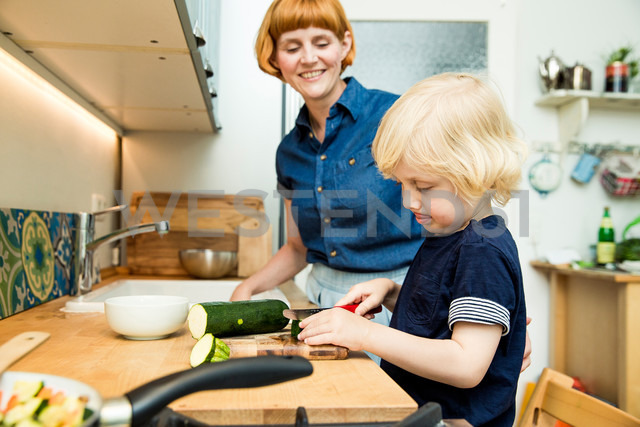 Littel boy chopping vegetables in the kitchen while his mother watching him - SPFF00016