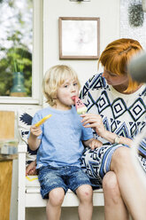 Mother and little son sitting on balcony eating ice lollies - SPFF00037