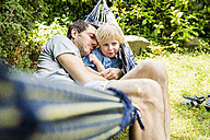Father and his little son together in hammock in the garden - SPFF00043