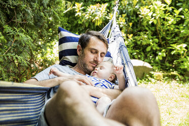 Portrait of father and his baby son together in hammock in the garden - SPFF00046