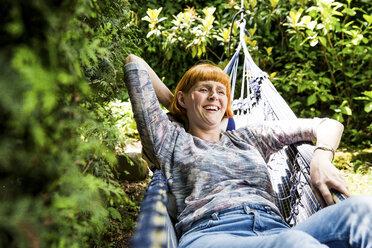 Portrait of laughing woman lying in hammock in the garden - SPFF00049