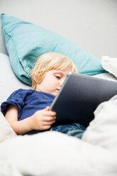 Little boy lying on bed using tablet - SPFF00052