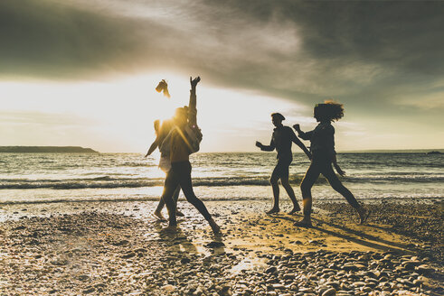 Excited friends on the beach at sunset - UUF11646