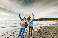 Happy friends making soap bubbles on the  beach - UUF11661