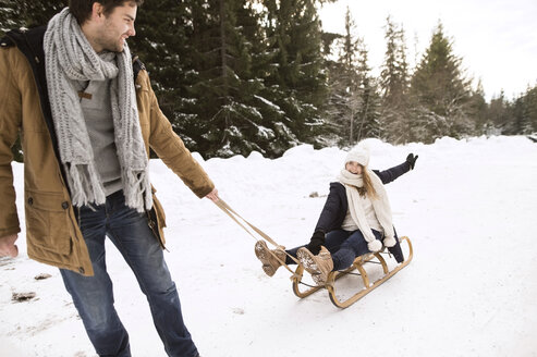 Happy young couple with sledge in winter forest - HAPF02032