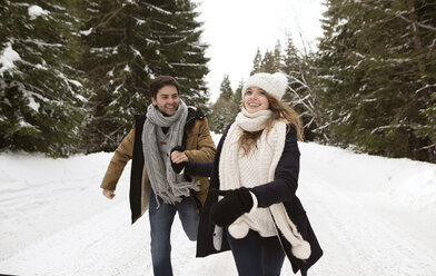 Happy young couple running in snow-covered winter landscape - HAPF02035