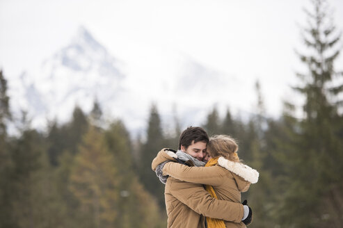 Happy young couple hugging each other in winter landscape - HAPF02038
