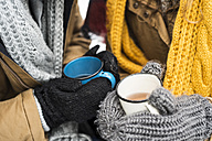 Young couple wearing gloves holding cups of tea in winter, close-up - HAPF02050