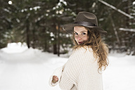 Portrait of smiling young woman wearing hat and knit pullover in winter forest - HAPF02053