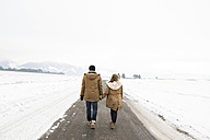 Back view of young couple in love walking hand in hand on country road in snow-covered landscape - HAPF02056