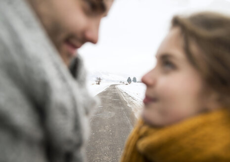 Empty country road in snow-covered landscape with young couple in love in the foreground - HAPF02059