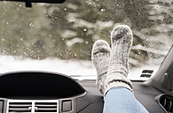 Woman sitting in car with feet up on dashboard - HAPF02068