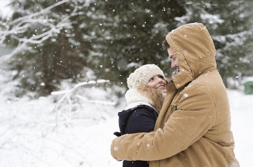 Happy young couple standing face to face in snow-covered winter forest - HAPF02071