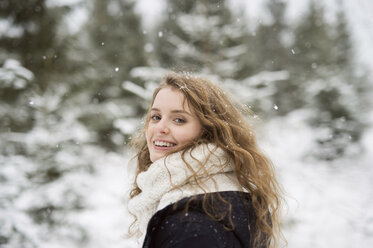 Portrait of smiling young woman in winter forest - HAPF02074