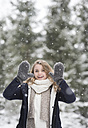 Portrait of happy young woman at snowfall in nature - HAPF02077