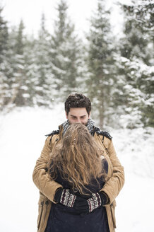 Happy young couple hugging each other in winter landscape - HAPF02080