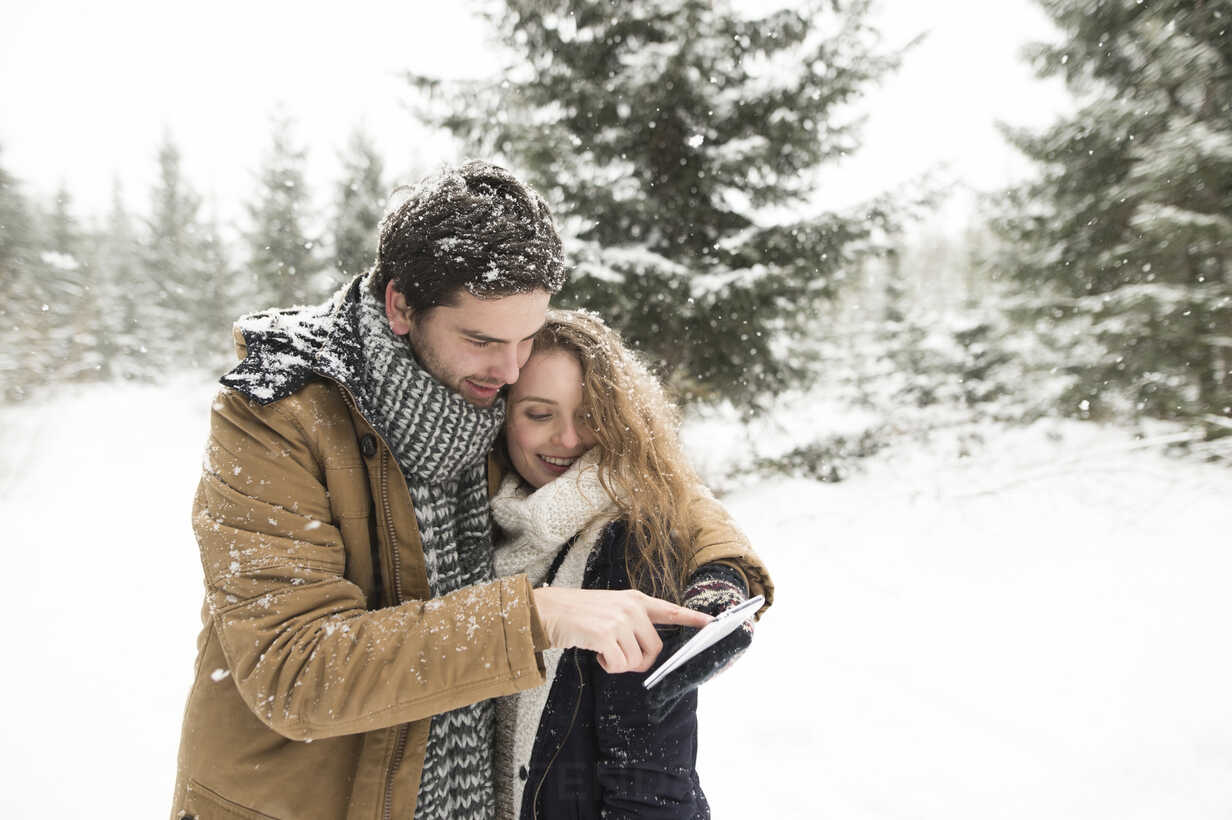Happy young couple standing in snow-covered winter forest using cell phone - HAPF02086 - HalfPoint/Westend61