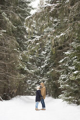 Happy young couple standing face to face in snow-covered winter forest - HAPF02092