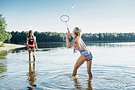 Two friends playing shuttlecock at lakeshore - MJF02186