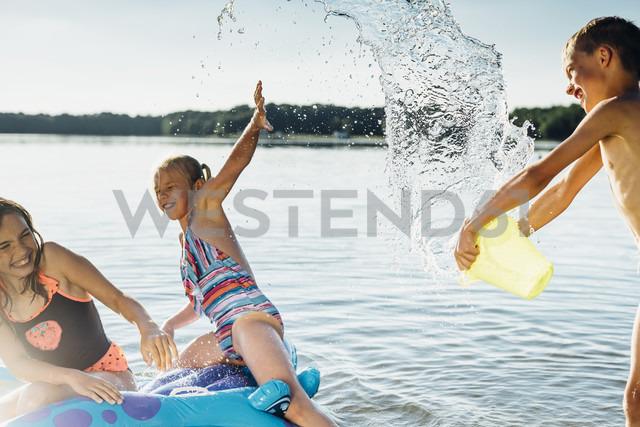Boy splashing with water at lakshore - MJF02189