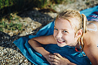 Portrait of smiling blond girl lying on towel on the beach - MJF02192