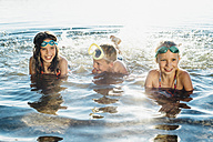 Three smiling friends splashing with water at lakeshore - MJF02198