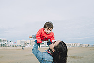 Mother holding up baby girl on a winter day on the beach - GEMF01776