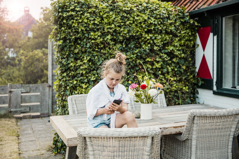 Girl sitting on terrace table using cell phone - MOEF00066