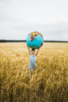Girl standing in grain field holding globe - MOEF00075