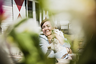 Woman cuddling with dog on terrace - MOEF00078