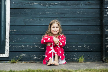 Girl wearing bathrobe outdoors sitting at wooden hut with toy wind turbine - MOEF00087