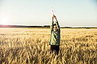 Girl standing in grain field holding miniature wind turbine - MOEF00093
