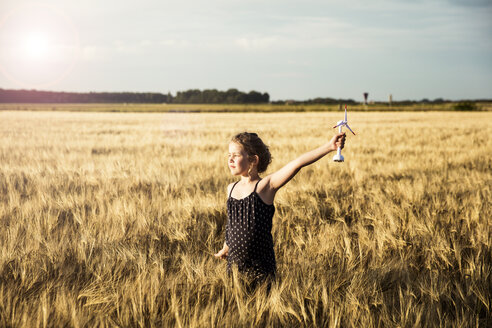 Girl standing in grain field holding miniature wind turbine - MOEF00096