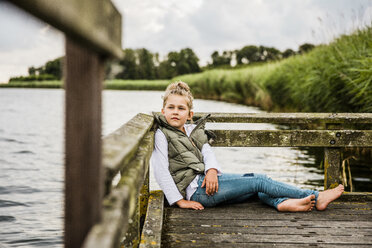 Girl sitting on jetty at a lake - MOEF00105