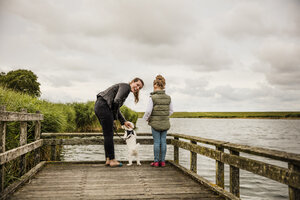 Mother and daughter standing on jetty at a lake with dog - MOEF00108
