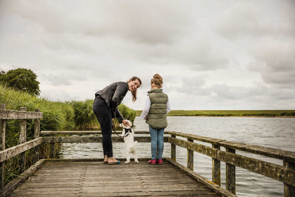 Mother and daughter standing on jetty at a lake with dog - MOEF00108 - Robijn Page/Westend61