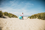 Girl with globe on the beach - MOEF00120