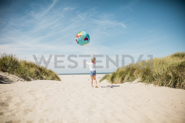 Girl playing with globe on the beach - MOEF00123