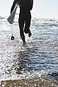 Portugal, Algarve, man running in the water with surfboard - JRF00324