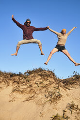 Portugal, Algarve, couple on the beach jumping down dune - JRF00339