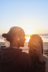 Portugal, Algarve, affectionate couple on the beach at sunset - JRF00345