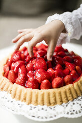 Girl's hand taking strawberry from cake - MOEF00137
