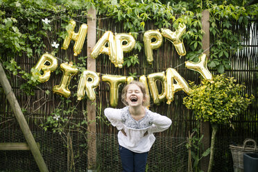 Portrait of laughing girl in the garden with decoration for Birthday Party in the background - MOEF00140