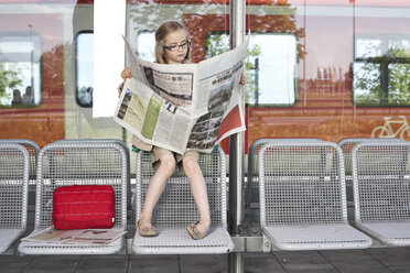 Portrait of little girl sitting at platform reading newspaper - FSF00949